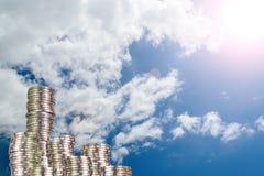 Colonnes des pièces de monnaie, piles des pièces de monnaie disposées comme graphique sur le ciel bleu Photographie stock libre de droits