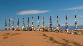 Colonnes en bois sacrées avec les rubans colorés, lac Baikal photo libre de droits