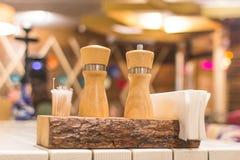 Coloqúese con la sal, la pimienta, los palillos y las servilletas en la tabla en el restaurante Fotografía de archivo libre de regalías