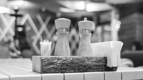Coloqúese con la sal, la pimienta, los palillos y las servilletas en la tabla en el restaurante en b/w Foto de archivo libre de regalías