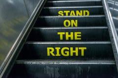 Coloqúese en el aviso derecho en una escalera móvil Foto de archivo libre de regalías