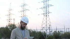 Coloque al director técnico con los dibujos de funcionamiento en la central nuclear Trabajador en el casco blanco con la ingenier almacen de video
