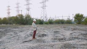 Coloque al director técnico con los dibujos de funcionamiento en la central nuclear Trabajador en el casco blanco con la ingenier metrajes