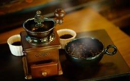 Coloque completamente dos feijões de café na madeira com vintageold, clássico foto de stock