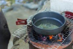 Coloque el aceite en una cacerola, coloqúelo en la estufa, prepare el desayuno para caminar o acampar usando como concepto del vi Fotografía de archivo