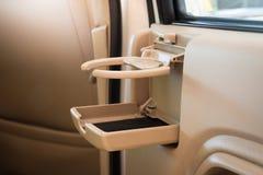 Coloque el café de las FO o las tazas o botella del té en la consola del vehículo en coche de lujo moderno Fotografía de archivo