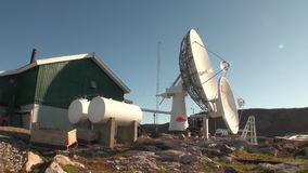 Coloque la antena de satélite en montañas en la orilla de Groenlandia en el Océano ártico metrajes