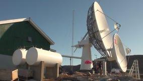 Coloque la antena de satélite en la orilla de Groenlandia en el Océano ártico almacen de video