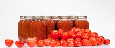 Coloque los tomates con los tarros de salsa de tomate conservada Fotografía de archivo