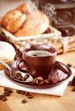 Coloque o café quente com feijões e doces de chocolate Fotografia de Stock Royalty Free