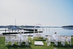 Coloque o local de encontro para a cerimônia de casamento pelo mar cadeiras brancas e arco solene antes do casamento foto de stock royalty free