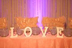 Coloque solamente la placa de marfil de las letras que lee 'amor 'y la vela del té cristalino grita colocado en la tabla de novia imagen de archivo