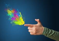 Coloré éclabousse sortent des mains formées par arme à feu Photographie stock