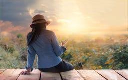 Coloré abstrait, femme détendant avec le smartphone à disposition dessus dehors en nature rurale de coucher du soleil photos stock