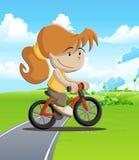 Coloré d'une fille faisant du vélo par le champ Photographie stock