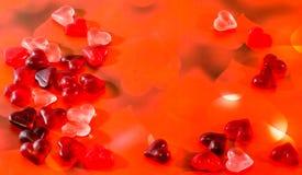 Coloré (rose, rouge et orange), gelées transparentes de forme de coeur, fond rouge de lumière de coeur Photo libre de droits