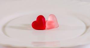 Coloré (rose, rouge et orange), la forme transparente de coeur gèle avec le plat en céramique, d'isolement Photo stock