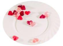Coloré (rose, rouge et orange), la forme transparente de coeur gèle avec le plat en céramique, d'isolement Image stock