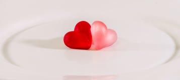 Coloré (rose, rouge et orange), la forme transparente de coeur gèle avec le plat en céramique, d'isolement Photo libre de droits