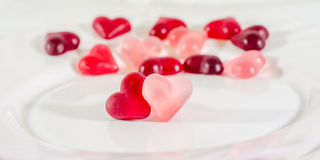 Coloré (rose, rouge et orange), la forme transparente de coeur gèle avec le plat en céramique, d'isolement Photographie stock