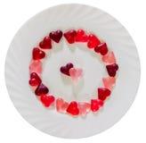 Coloré (rose, rouge et orange), la forme transparente de coeur gèle avec le plat en céramique, fond blanc Photos stock