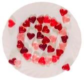 Coloré (rose, rouge et orange), la forme transparente de coeur gèle avec le plat en céramique, fond blanc Photographie stock