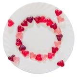 Coloré (rose, rouge et orange), la forme transparente de coeur gèle avec le plat en céramique, fond blanc, d'isolement Image stock