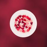 Coloré (rose, rouge et orange), la forme transparente de coeur gèle avec le plat en céramique, fond coloré de texture de degradee Images libres de droits