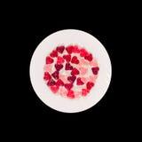 Coloré (rose, rouge et orange), la forme transparente de coeur gèle avec le plat en céramique, fond noir, d'isolement Photo stock