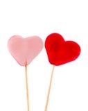 Coloré (rose, rouge et orange), la forme transparente de coeur gèle dans des bâtons en bois, fond blanc Images stock