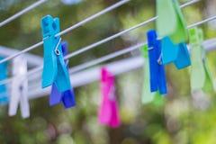 Coloré vêtez les chevilles sur une corde à linge photo stock