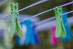 Coloré vêtez les chevilles sur une corde à linge photographie stock