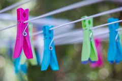 Coloré vêtez les chevilles sur une corde à linge photos stock