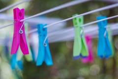 Coloré vêtez les chevilles sur une corde à linge images stock