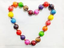 Coloré woodden les perles en forme de coeur Photo libre de droits