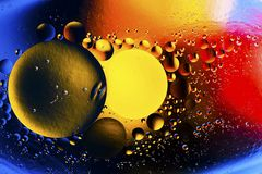 Color abstract background based on red, yellow, orange and brown circles and ovals. Emulsion of water and oil on a colored background. Beautiful color abstract Royalty Free Stock Photo