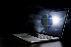 Color aerostat on laptop screen. Mixed media Stock Images