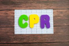 Color alphabet in word CPR abbreviation of Cardiopulmonary resuscitation lies on wood background. Color alphabet in word CPR abbreviation of Cardiopulmonary stock photos