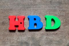 Color alphabet in word HBD Abbreviation of happy birthday. On wood background stock photography
