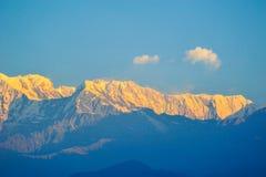 Color anaranjado de la salida del sol encima de la montaña de la nieve contra el cielo azul Fotos de archivo