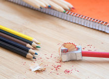 Color art pencils with sharpener and notebook Stock Photos