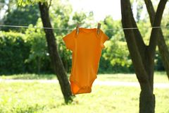 Color baby onesie hanging on clothes line. Outside stock photography