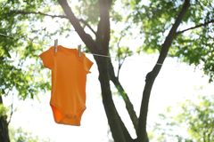 Color baby onesie hanging on clothes line outside. Space for text stock image