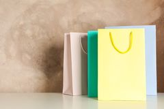 Color bags on white table against brown background royalty free stock photo