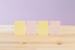 Color blank sticky notes on wooden desk Stock Photos