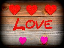 Color boosted red and pink hearts on wood plank background that. Beautiful very colorful red and pink hearts on wood plank background that says Love with copy Stock Photo