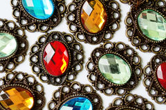 Color brooches. Multicolor vintage brooches on white background Stock Photos