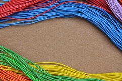 Color cables on brown felt Stock Photography