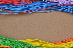 Color cables on brown felt Royalty Free Stock Images