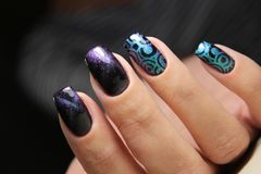 Color cat& x27;s eye manicure with a nail polish. Bottle in hand royalty free stock photo